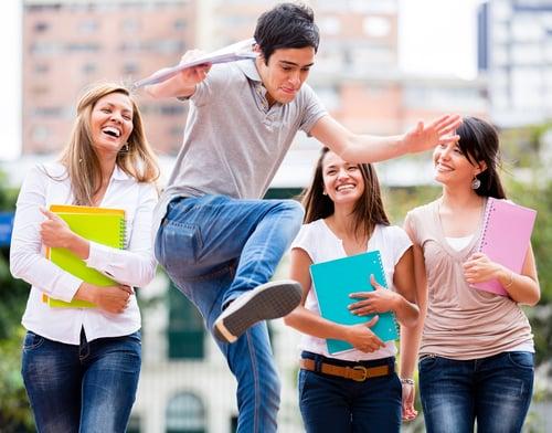 Group of students having fun looking at a man jumping