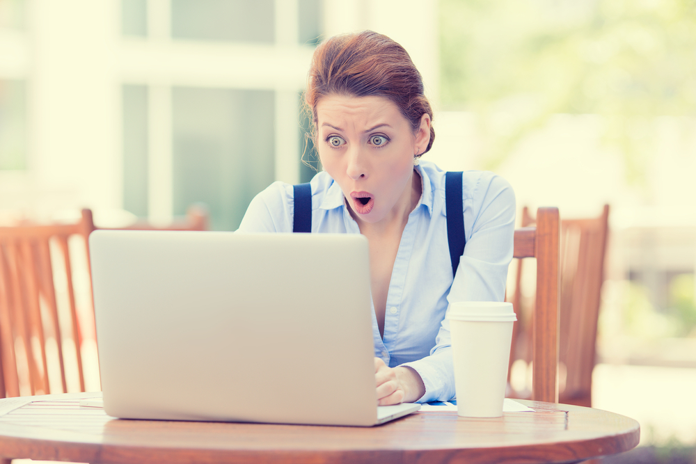 Shocked young business woman using laptop looking at computer screen blown away in stupor sitting outside corporate office. Human face expression, emotion, feeling, perception, body language, reaction