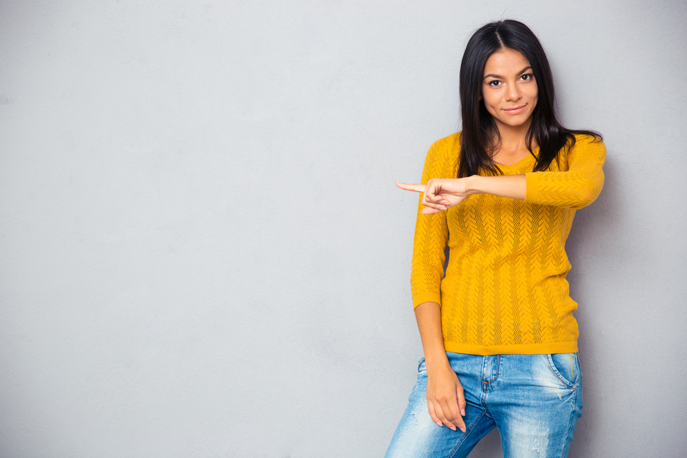 Smiling casual woman in sweater showing finger away over gray background