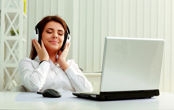 Young beautiful businesswoman listening music in headphones at office